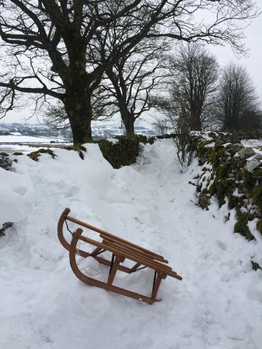 Snow in Cumbria - sledge in a laneway