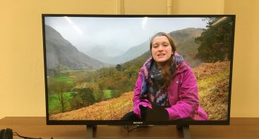 A large television screen, showing Katie sitting on a misty mountainside, speaking to the camera