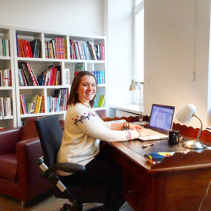 Katie sitting at a desk in a light airy room in a Brussels apartment, with shelves of books behind her