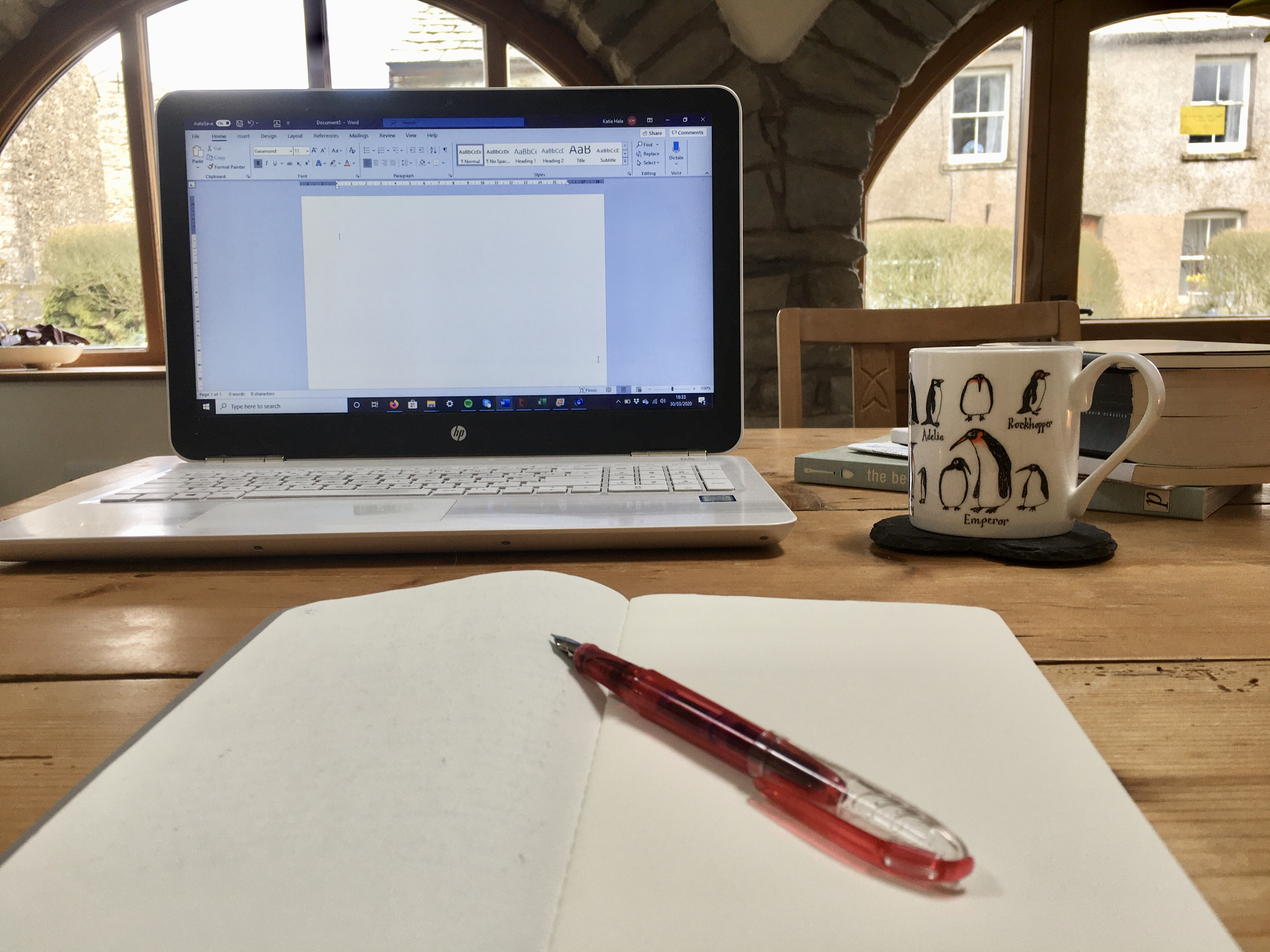 Notebook, pen, laptop and coffee mug on a kitchen table