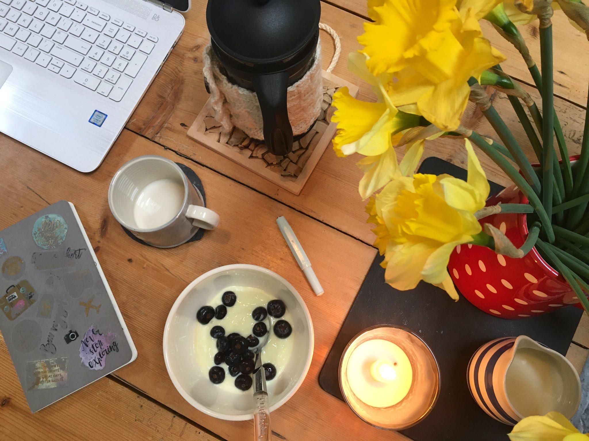Notebook and laptop on a kitchen table from above, with coffee, breakfast and a candle