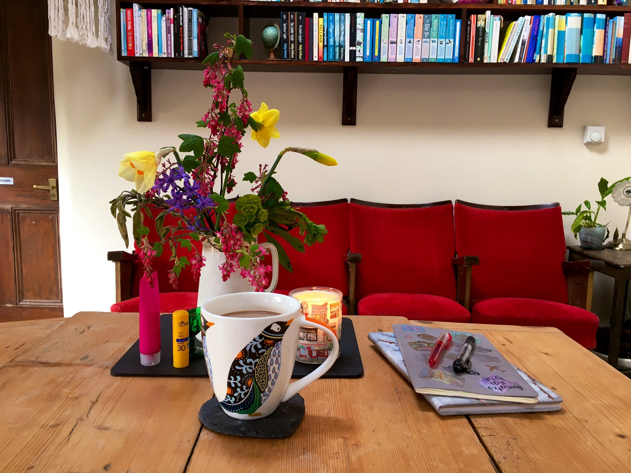 Kitchen table, with notebooks, pens, coffee and a vase of flowers. In the background, theatre seats and the bottom of a set of wall-mounted bookshelves.