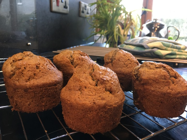 Freshly baked carrot cake muffins on a cooling rack