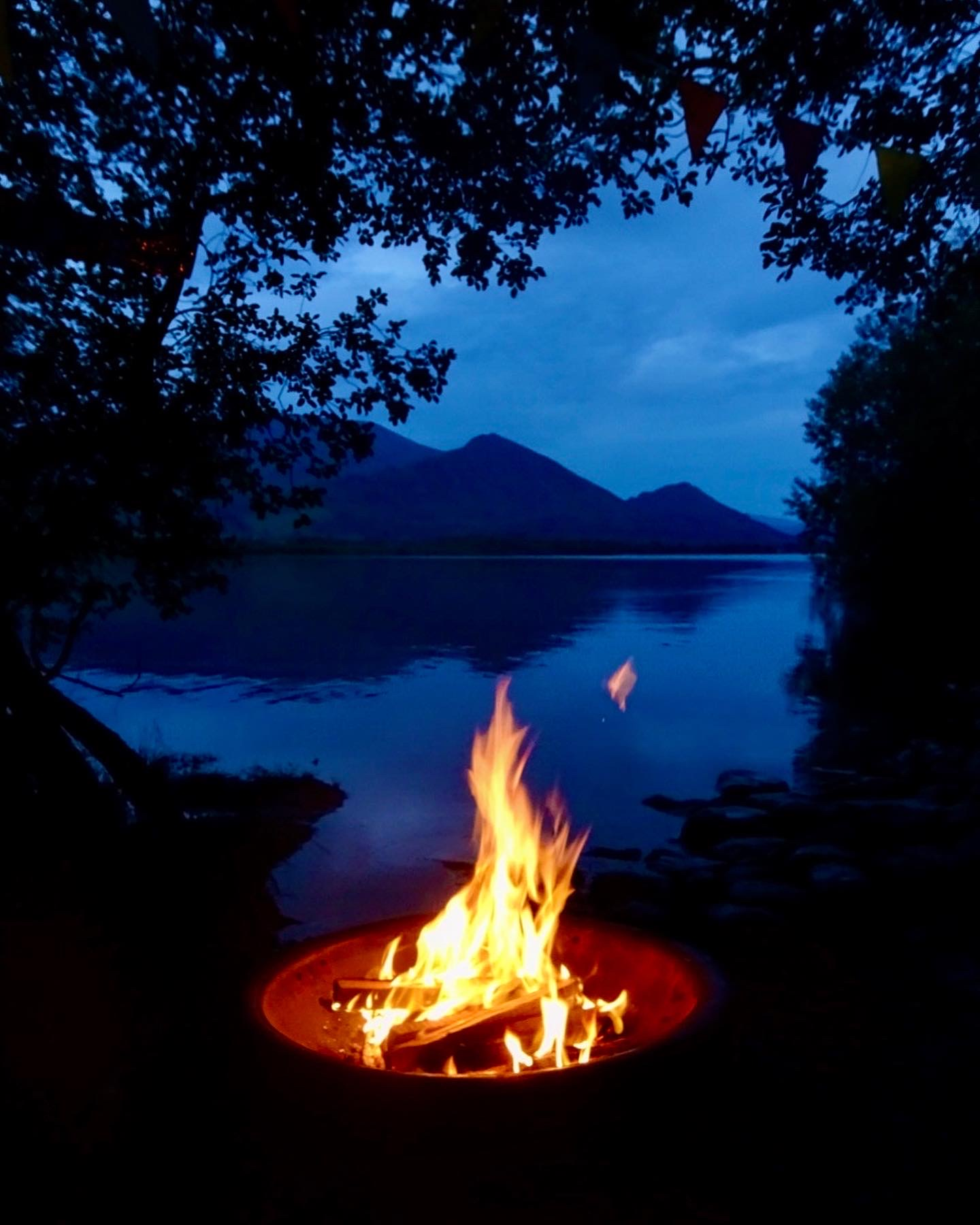Nighttime; lake and mountains through a gap in the trees; on a stony beach, a brazier with a campfire burning
