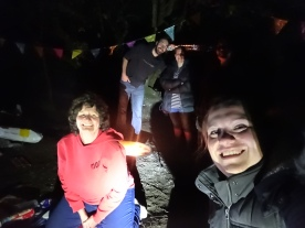 A group of people by torchlight, smiling