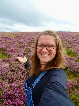 Katie wearing glasses and dungarees and smiling at the camera; behind, purple heather stretching away across the fell