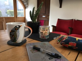 A kitchen table, with a cactus, a lit candle, a notebook and pen, and a mug of coffee