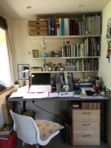 A desk covered in bits of manuscript, with shelves of notebooks above