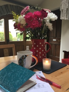 A jug of flowers, a lit candle, a mug of coffee, a notebook and a pen on a kitchen table