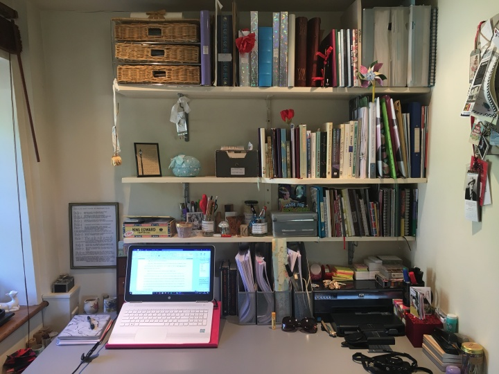 A tidy desk with a laptop on it and shelves with notebooks above