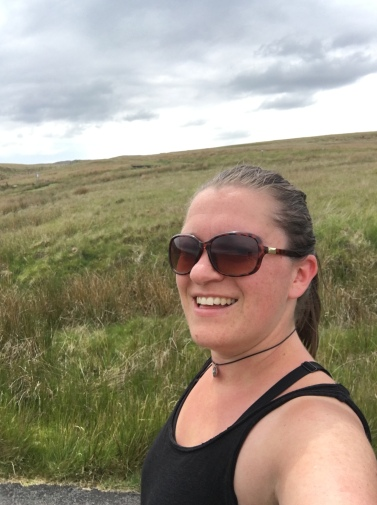 Katie in running gear and sunglasses, smiling at the camera