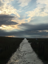 Wet road leading over the horizon, with a cloudy post-storm sky overhead