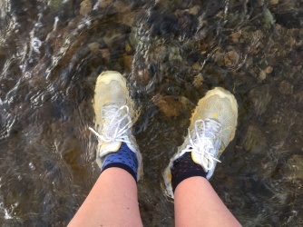 Looking down at feet wearing trainers, submerged in floodwater