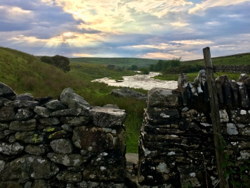 A dry stone wall with a stile in it. Beyond it, the River Lowther, and a cloudy sky above, with god rays shining through