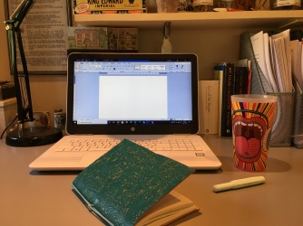 Writing desk with a laptop, notebook, pen and beaker of juice