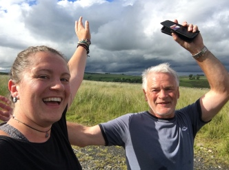 Katie and her dad with their arms in the air, smiling at the camera