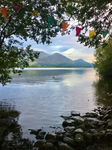 View of a lake and mountains through a gap in the trees; multi-coloured bunting strung between them