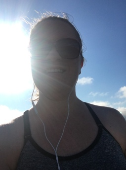 Katie with sunglasses and earbuds, smiling down at the camera with a blue sky and the sun behind her