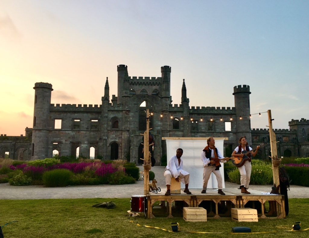 Three actors playing musical instruments on a temporary stage, with a festoon of lights above it; a silhouetted castle and a sunset in the background