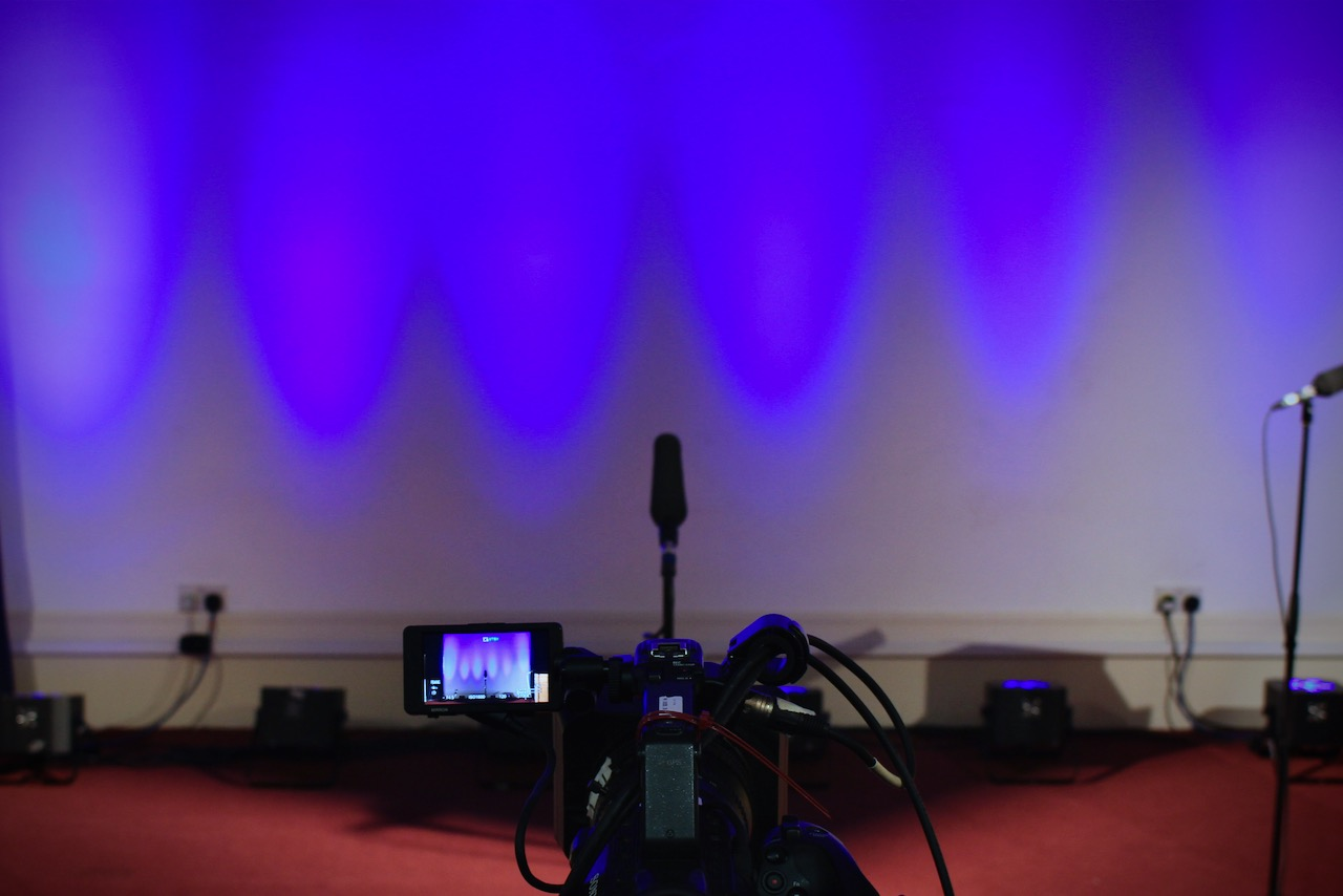camera pointing at a microphone and blue-lit stage space
