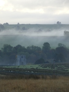 Valley with the ruined tower of Shap Abbey in the bottom, and ground mist rising from the fields