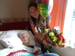 katie standing beside her grandma, holding a baloon and a bunch of flowers