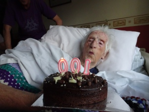 woman blowing out candles in the shape of '100' on a birthday cake