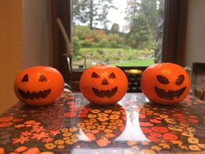 three satsumas in a row, with pumpkin faces drawn on them in marker pen